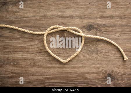 Forme de coeur faites de corde sur le vieux bois Banque D'Images