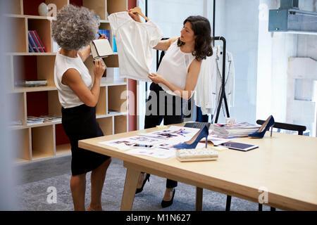 Deux femmes discuter de vêtements dans un bureau des médias créatifs Banque D'Images