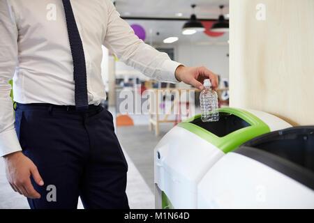 L'homme dans une bouteille en plastique de recyclage dans les bureaux, Close up Banque D'Images