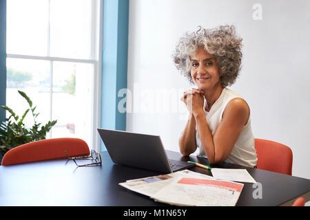 Femme d'âge moyen de travailler dans un bureau en souriant à l'appareil photo Banque D'Images