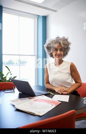 Femme d'âge moyen dans un bureau souriant pour appareil photo, à la verticale Banque D'Images