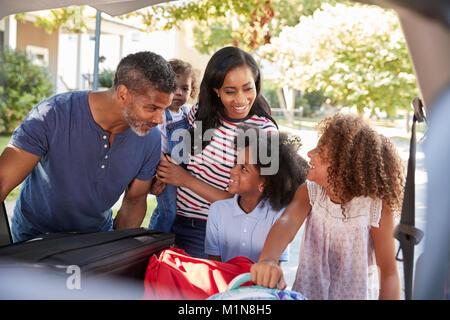 Famille qui part en vacances en voiture charger des bagages Banque D'Images