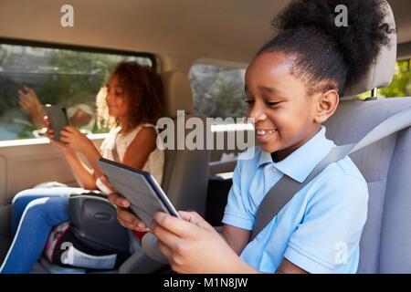 Les enfants en utilisant des appareils numériques sur Voiture Banque D'Images