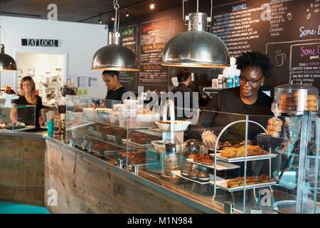 Le personnel travaillant dans les présentoirs de comptoir café occupé Banque D'Images