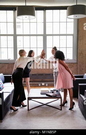 Collègues femmes high cinq à la réunion occasionnelle, vertical Banque D'Images