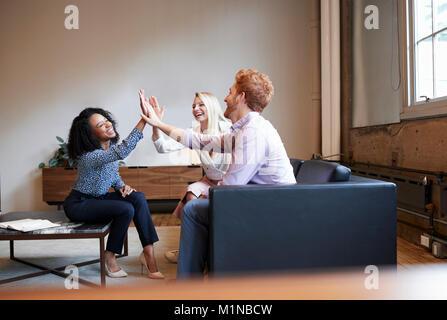Trois collègues des cinq lors d'une réunion de travail occasionnel Banque D'Images