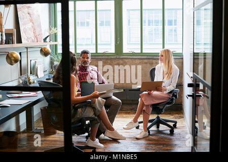 Trois collaborateurs dans une réunion d'équipe, vu à travers la porte ouverte Banque D'Images