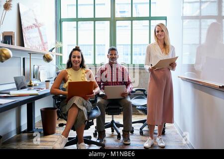 Trois collaborateurs dans une réunion d'équipe à la recherche à l'appareil photo Banque D'Images