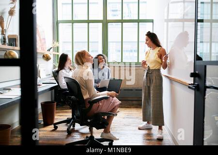 Femme debout au tableau blanc lors d'une réunion avec l'équipe féminine Banque D'Images