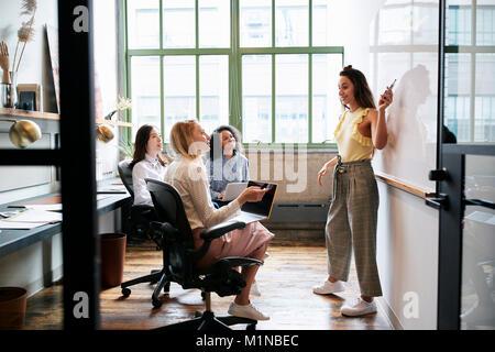 Woman pointing at whiteboard lors d'une réunion avec l'équipe féminine Banque D'Images