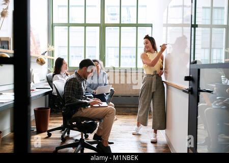 Femme à l'aide de tableau blanc dans une petite réunion de l'équipe Banque D'Images