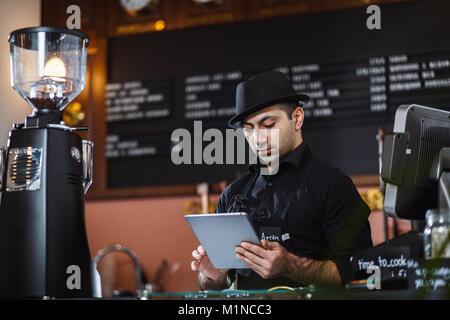 Portrait de barista holding digital tablet in coffee shop.