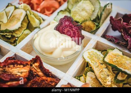 Des jetons colorés de différents légumes frais dans une boîte en bois blanc sur un fond blanc. Isolées. Banque D'Images