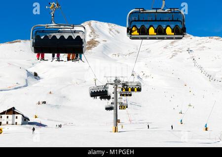 Les skieurs de monter sur le télésiège contre ciel bleu- Station de ski en Italie le jour de l'hiver ensoleillé Banque D'Images