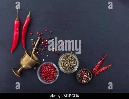 Divers Le poivre et les piments et un moulin à poivre noir en laiton sur fond de pierre, vue du dessus, copy space Banque D'Images