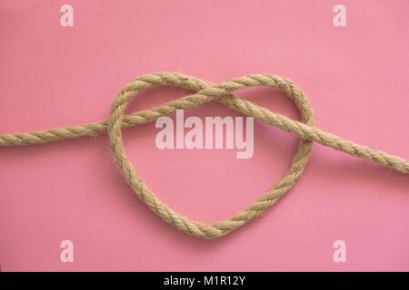 Forme de coeur à partir de la corde sur fond rose Banque D'Images