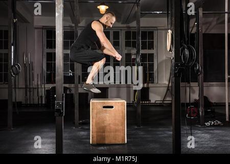 Jeune athlète homme faisant un saut de l'exercice dans la salle de sport Banque D'Images