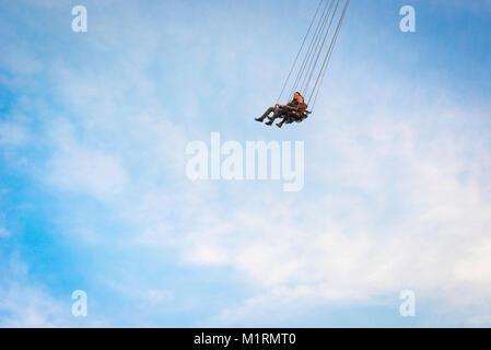 De haut vol, un couple profitez d'un trajet sur le Prater Turm (tour) président-swing dans le célèbre parc d'attractions Banque D'Images