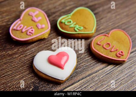 Belle en rouge épice glaze en forme de cœur sur un fond de bois. Banque D'Images