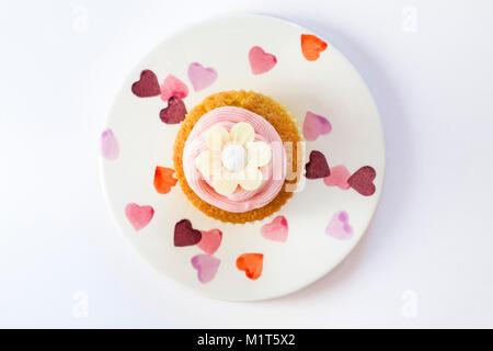 Gâteau cupcake fait maison avec du glaçage rose fraise cerise et papier de riz fleurs daisy comestibles, sur la Banque D'Images