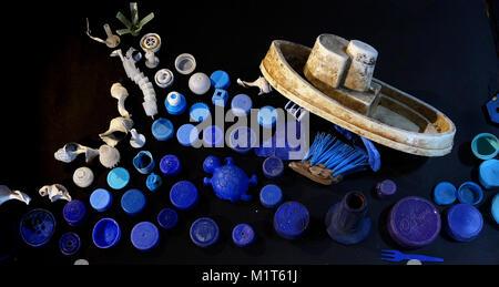 Un jouet bateau navigue le déchaussement par le mer de déchets en plastique. Banque D'Images