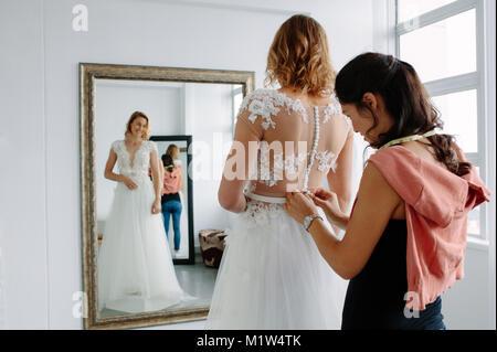 Assistant femme femme aidant à essayer robe de mariée dans une boutique. Propriétaire de magasin nuptiale aider Banque D'Images