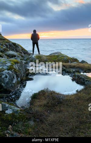 L'homme sur la côte rocheuse pendant le coucher du soleil à Stora Lund, Suède