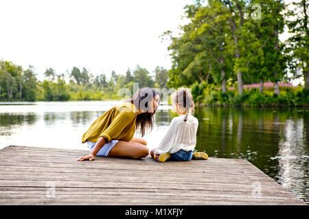 Mère et fille sur la jetée au bord du lac en Friseboda, Suède Banque D'Images