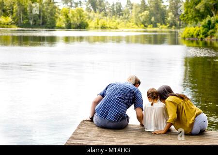 Famille sur la jetée au bord du lac en Friseboda, Suède Banque D'Images