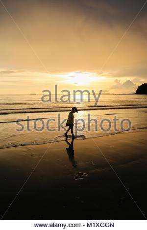 Garçon à la plage pendant le coucher du soleil à Ko Lanta, Thaïlande Banque D'Images