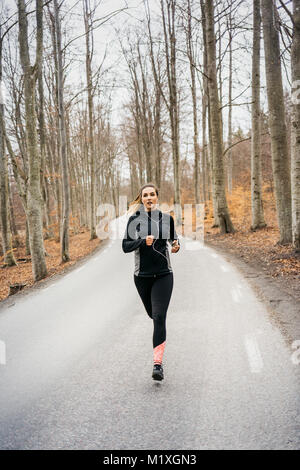 Young woman running on rural road dans Sodermanland, Suède Banque D'Images