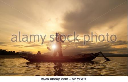 Silhouette de bateau en bois pêcheur sur Myanmar Myanmar ,en action pêcheur attraper les poissons d'eau douce dans Banque D'Images