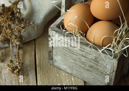 Brown oeufs biologiques sur la paille dans la boîte en bois Vintage sur Plank Table de cuisine , Fleurs sèches serviettes. Banque D'Images