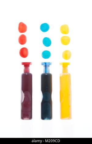 Trois conteneurs de rouge, bleu et jaune taches liquides, studio shot. Banque D'Images