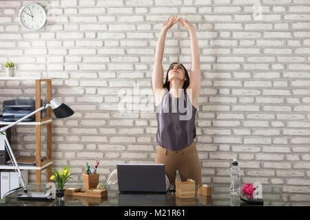 Young Businesswoman Stretching à vert au travail Banque D'Images