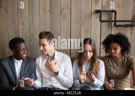 À l'aide d'amis multiraciale millénaire téléphones mobiles et parler un Banque D'Images