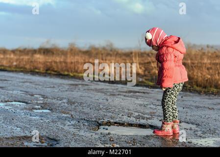 Concept - enfance heureuse. Petite fille à la recherche dans la flaque, aire de plaisir, des moments inoubliables, Banque D'Images