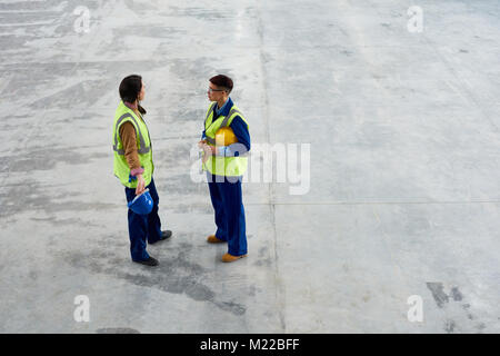 High angle portrait de deux jeunes femmes travaillant à l'usine de parler les uns aux autres articles du grand atelier, Banque D'Images