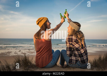 Deux meilleurs amis assis sur le littoral à l'amitié de brunissage Banque D'Images