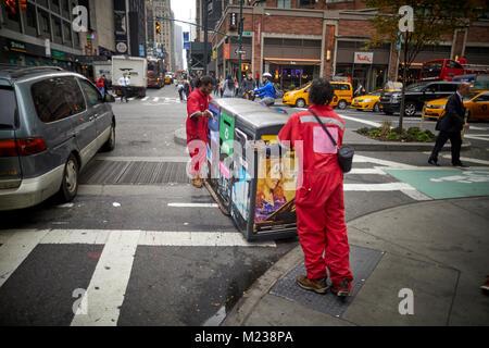 New York City Manhattan, Times Square street cleaners le déplacement d'une poubelles de recyclage Banque D'Images