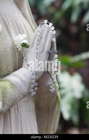 Statue de pierre, priant hands holding rosary Banque D'Images