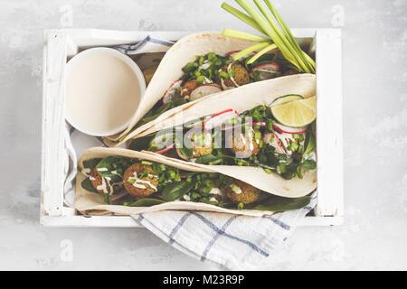 Falafels végétaliens avec légumes et sauce tahini dans la tortilla dans une boîte en bois blanc pour un pique-nique. Vegan aliments sains, l'Arabe de la nourriture.