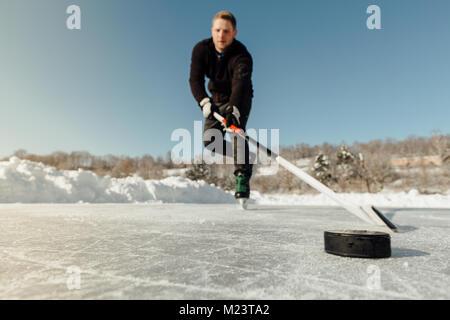 Man playing ice hockey sur un lac gelé en se concentrant sur un puck Banque D'Images