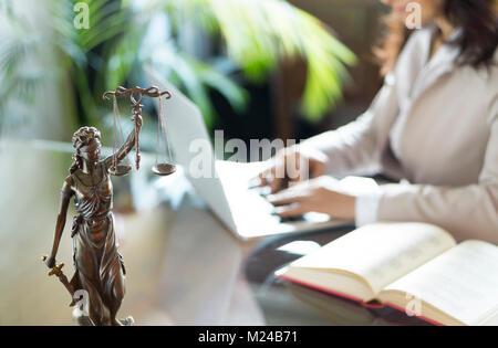 Bureau de l'avocat. Statue de la Justice avec des échelles et juriste travaillant sur un ordinateur portable. Des Banque D'Images