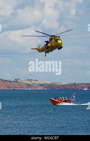 Exercice d'entraînement de l'Air Sea Rescue jaune avec l'hélicoptère Sea King et bateau gonflable rigide de la RNLI. Banque D'Images