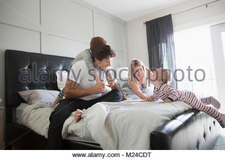 Famille ludique on bed Banque D'Images