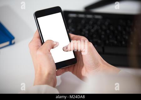 Close-up of a person's Hand Holding Smart Phone avec écran blanc Banque D'Images