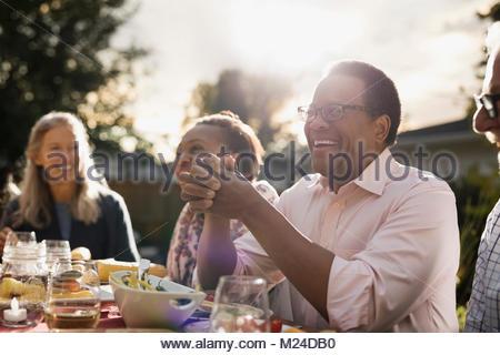 Laughing man enjoying garden party le déjeuner avec des amis à table patio ensoleillé Banque D'Images