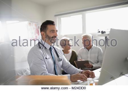 Homme Un médecin travaillant à l'ordinateur portable avec le couple patient en contexte en médecin Banque D'Images