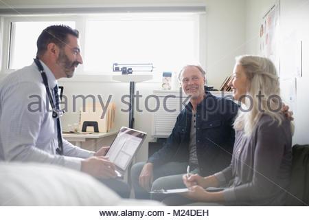 Médecin Homme avec portable parlant à senior couple patient en salle d'examen Banque D'Images